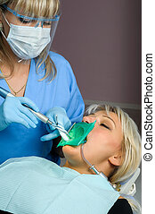 dentist with patient, using dental curing light - dentist at...