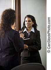 Hispanic businesswoman and colleague conversing