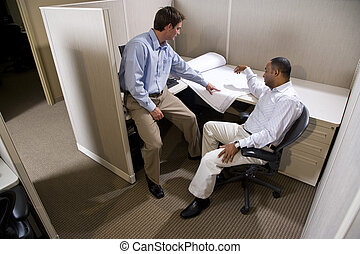 Two male colleagues working in cubicle with blueprints