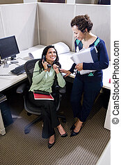 Two Hispanic female colleagues meeting in office cubicle