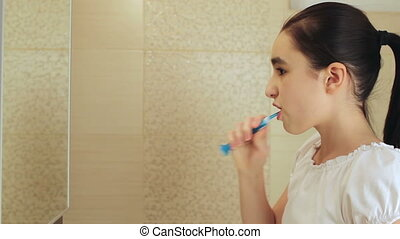 Brushing teeth - Cute little girl intensely brushing her...