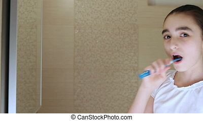 Young girl brushing teeth - Cute little girl intensely...