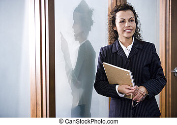 Close up of confident Hispanic businesswoman standing in boardroom, colleague standing outside