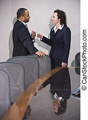 Multi-ethnic business executives conversing in boardroom -...