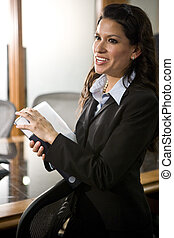 Confident young Hispanic businesswoman in boardroom