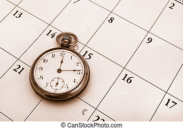 Time Management - A pocket watch sitting on a calendar...