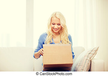smiling young woman opening cardboard box - transportation,...