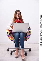 Cheerful woman sitting on the colourful chair with laptop