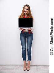 Full length portrait of a happy woman showing blank laptop...