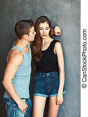fashion beautiful young couple on grey wall background