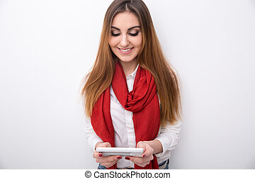 Smiling woman using smartphone over gray background