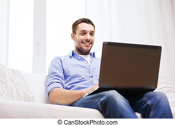 smiling man working with laptop at home - technology, home,...