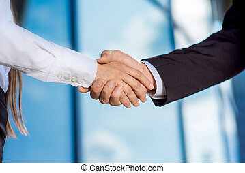 business couple shaking hands outdoors on contempopary...