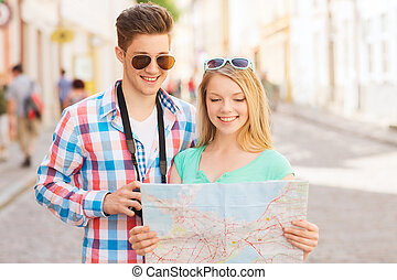 smiling couple with map and photo camera in city - travel,...