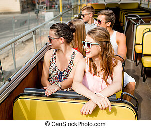 group of smiling friends traveling by tour bus - friendship,...