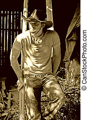 cowboy - handsome cowboy sitting on a ladder in barn looking...