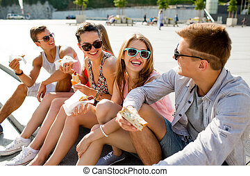 group of smiling friends sitting on city square -...
