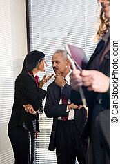 African American businessman and female colleague in private discussion