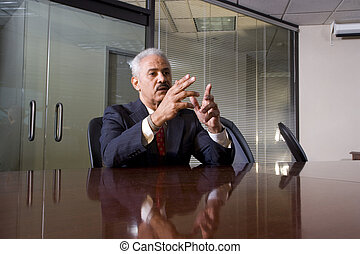 Serious African American businessman sitting at a boardroom table