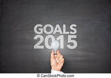 Goals 2015 on blackboard with businessman hand holding light...