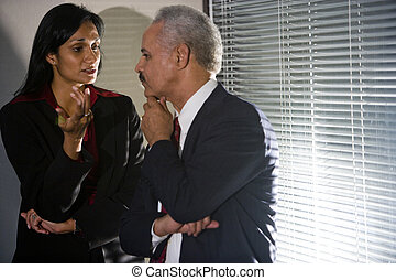 Multi-ethnic businesspeople having discreet conversation in...