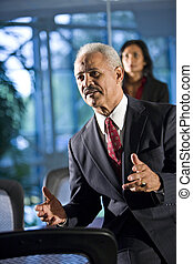 Mature businessman in boardroom meeting, colleague in background
