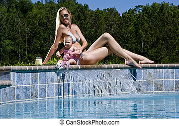 Mother and baby playing by swimming pool - Mother and six...