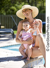 Mother with six month old baby next to a swimming pool