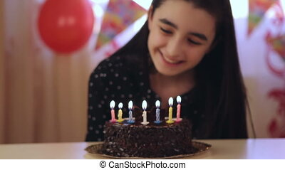Young girl enjoying birthday cake - Happy young girl blowing...
