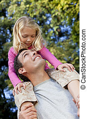 Father With Daughter On Shoulders Having Fun In A Park