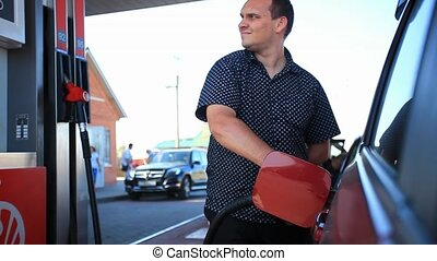 Young serious businessman refueling car tank at fuel station...