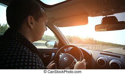 Serious man driving a car at sunset