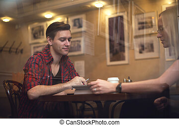 Couple is having a date in cafe. They drink coffee tea and...