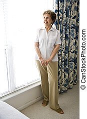 Cheerful elderly woman at home standing by a sunny window