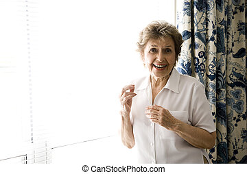 Cheerful senior woman at home standing by a sunny window