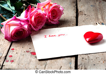 """Rose and a note with the text """"I love you"""" on a wooden..."""