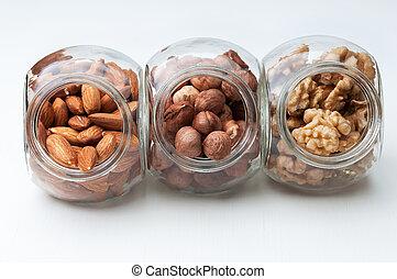 Walnut,almond and hazelnut in  glass jars on a white background.