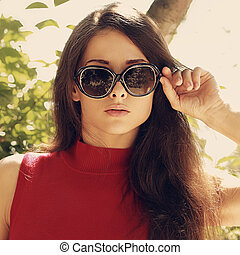 Fashion woman with long hair in modern sun glasses outdoors....