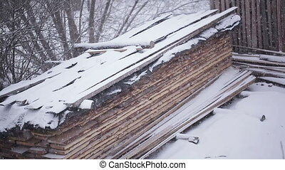 Stack boards - Snow-covered pile of wooden planks and...