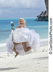 The young beautiful woman in a dress of the bride jumps at sea edge.