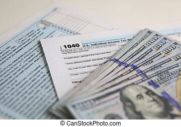 US Tax Form 1040 with new 100 US dollar bills. business...