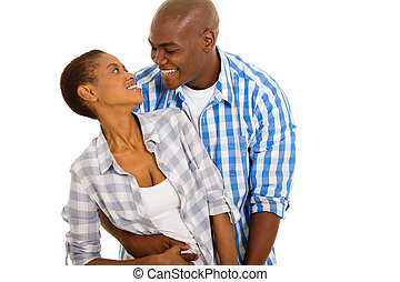 young african couple looking at each other - romantic young...