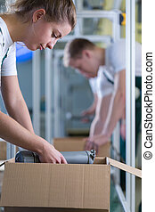 Girl packing the box - Young girl packing the box in...