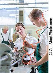 Machine operator - Young boss checking work of machine...