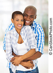 young african american couple hugging each other - cheerful...