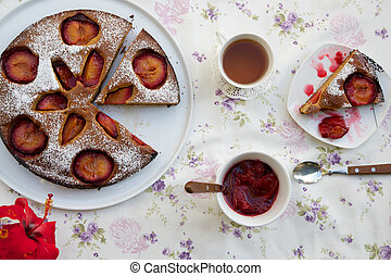 Tea time table- plum pie, plum marmalade in a white dish,cup...