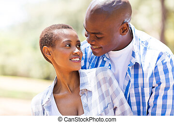 romantic young african couple embracing while looking at...