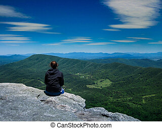 Hiker Looking Out Over Mountain Ran - A female hiker takes...