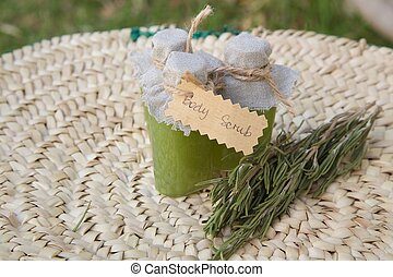 Rosemary body scrub and several rosemary branchlets in the...