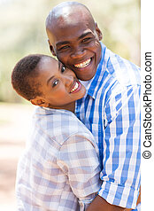 young black couple embracing outdoors